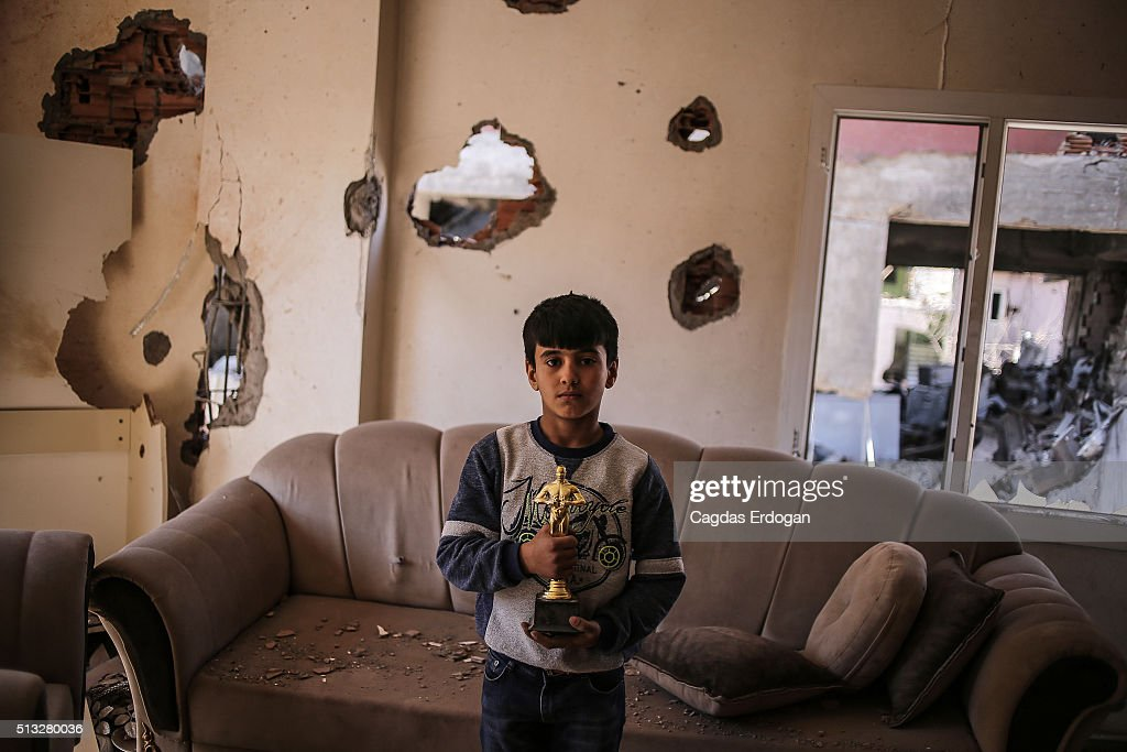 A boy holds a Oscar statuette in his ruined house on March 2 2016 in Cizre Turkey Turkish authorities scaled down a 24hour curfew imposed on the...