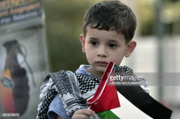 A boy holds a Palestinian flag near the Israeli embassy in Athens during a demonstration by Palestinians and supporting Greeks against Israeli air...