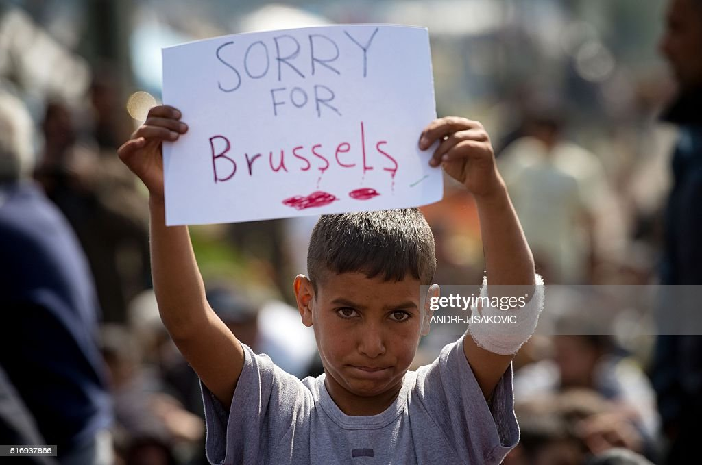 TOPSHOT - A boy holds a placard expressing sympathy for the victims of the terror attacks in Brussels during a protest at a makeshift camp at the Greek-Macedonian border near the village of Idomeni on March 22, 2016. Greece will not be able to start sending refugees back to Turkey from March 20, 2016, the government said, as the country struggles to implement a key deal aimed at easing Europe's migrant crisis. The numbers are daunting: officials said as of Saturday there were 47,500 migrants in Greece, including 8,200 on the islands and 10,500 massed at the Idomeni camp on the Macedonian border. / AFP / ANDREJ