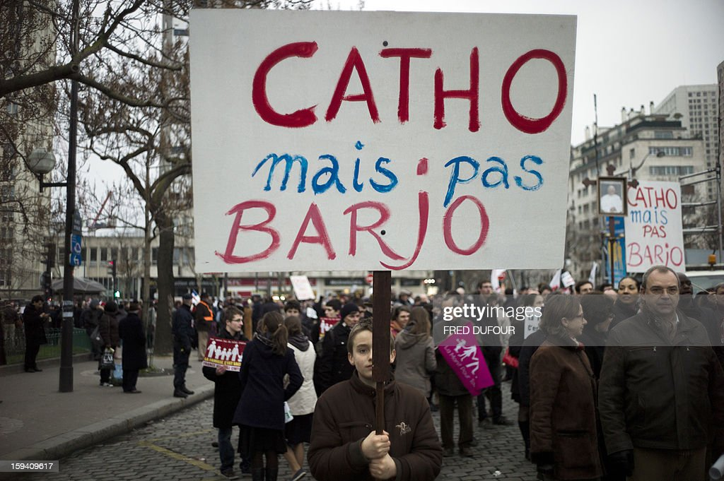 A boy holds a placard reading 'Catholics but not crazy' (Catho mais pas Barjo) during a march against same-sex marriage on January 13, 2013 in Paris. Tens of thousands march in Paris on January 13 to denounce government plans to legalise same-sex marriage and adoption which have angered many Catholics and Muslims, France's two main faiths, as well as the right-wing opposition. The French parliament is to debate the bill -- one of the key electoral pledges of Socialist President -- at the end of this month.