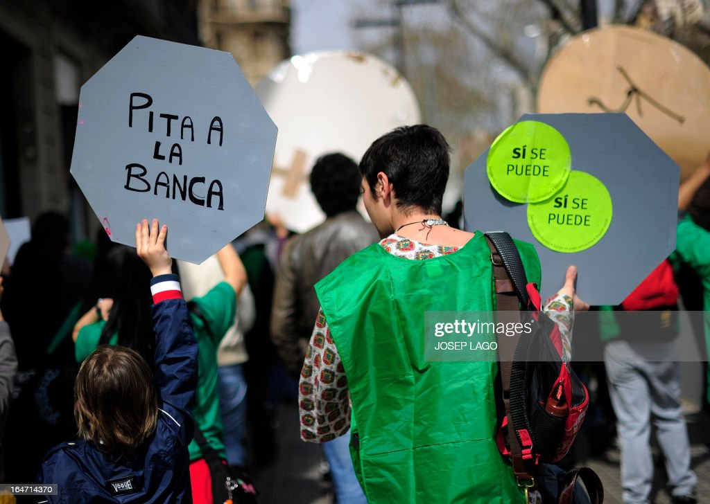 A boy holds a placard reading 'Lets catcall the bank' flanked by his mother as they take part in a protest by Platform for Mortgage Victims (PAH) to push for a new law to end a wave of evictions of homeowners ruined by the economic crisis, in Barcelona, on March 27, 2013. AFP PHOTO/ JOSEP LAGO