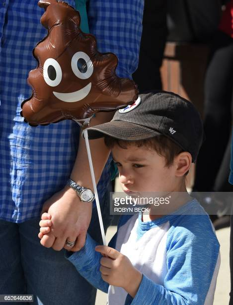 A boy holds a poo emoticon balloon as he joins his parents protesting against Breitbart News and what the protestors describe as the media company's...