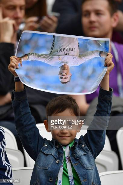 A boy holds a poster of Portugal's forward Cristiano Ronaldo before the 2017 Confederations Cup group A football match between Portugal and Mexico at...