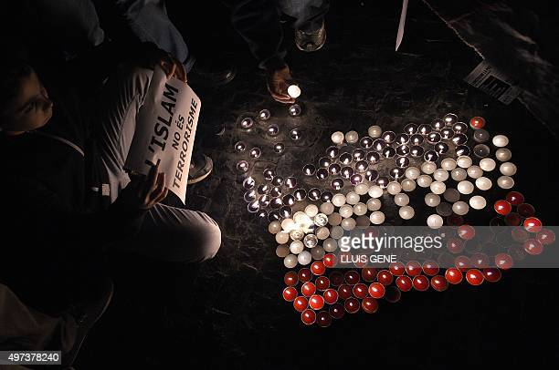 A boy holds a posters reading 'Islam is not terrorism' near candles in the colours of the French national flag during a demonstration called by the...