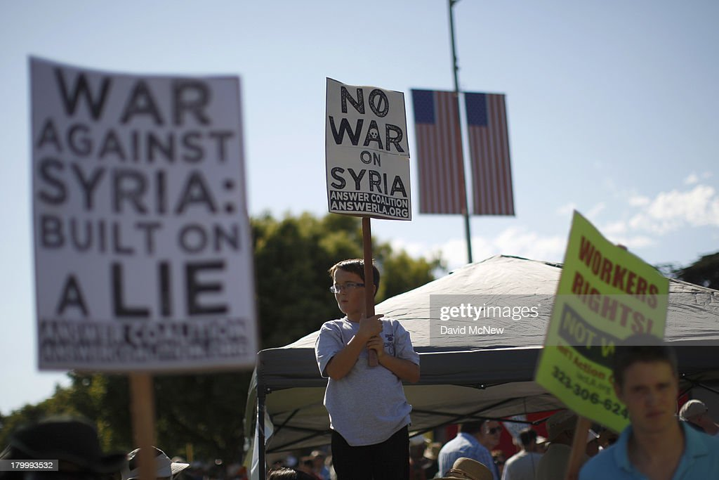 A boy holds a protest sign at a rally to urge Congress to vote against a limited military strike against the Syrian military in response to allegations that President Bashar Hafez al-Assad has used sarin gas to kill civilians on September 7, 2013 in Los Angeles, California. The Obama administration claims to have clear evidence that the Syrian military broke international law by killing nearly 1,500 Syrian civilians, including at least 426 children, in a chemical weapons attack on August 21, and is seeking the support of Congress for a missile strikes to prevent future chemical weapons attacks by the regime and other nations.