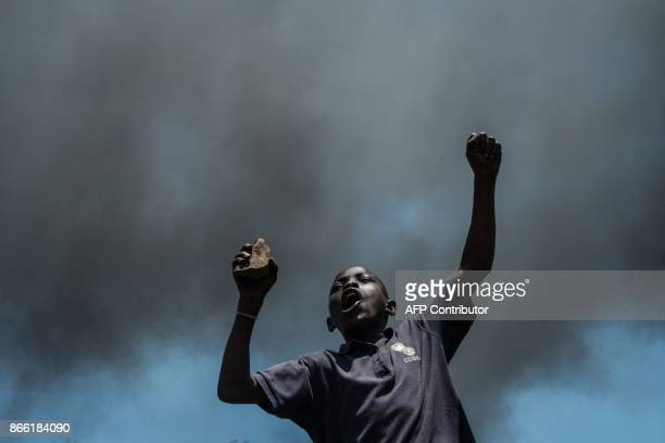 TOPSHOT A boy holds a rock during a demonstration of National Super Alliance presidential candidate Raila Odinga on the boycott of the upcoming...