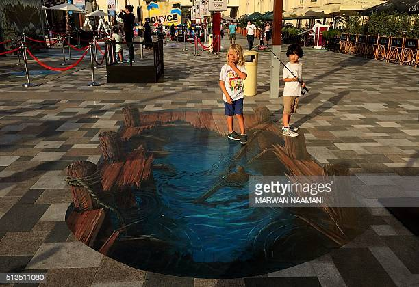 A boy holds a rod while interacting with a 3D artwork on March 3 2016 near the Jumeirah Beach Residence in Dubai during the Canvas Festival a...
