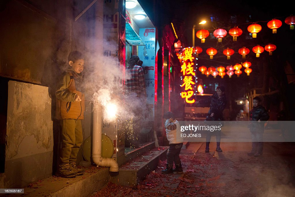 A boy holds a sparkler in an alleyway in Beijing during the lantern festival, which marks the end of celebrations for the Chinese new year period, on February 24, 2013. China celebrated the traditional lantern festival with food and fireworks as millions of migrant workers flowed back to the cities and smog blanketed a large part of the country. AFP PHOTO / Ed Jones