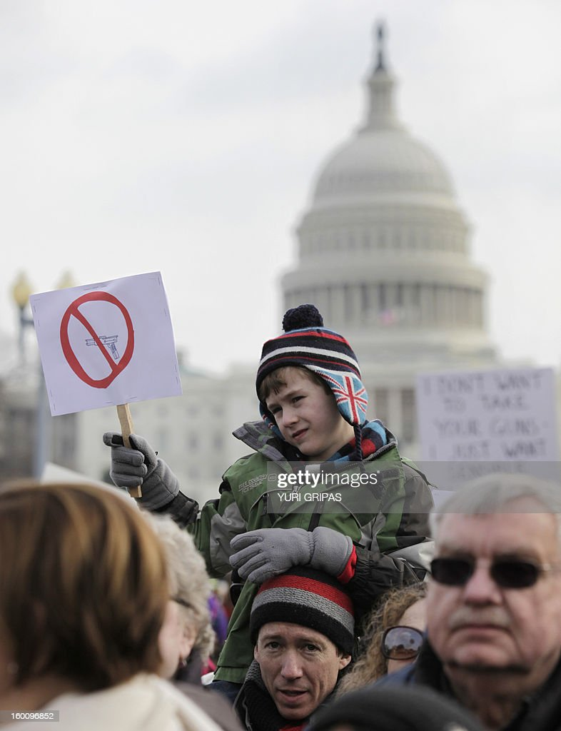 A boy holds an anti-gun poster during the March on Washington for Gun Control on January 26, 2013 in Washington in response to last month's school shooting in Newtown, Connecticut.