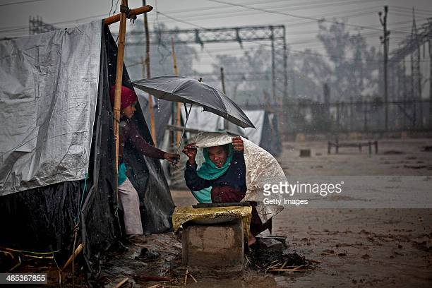 A boy holds an umbrella over his mother while she cooks during a rainstorm in the Jhola relief camp January 22 2014 in the Shamli district of Uttar...