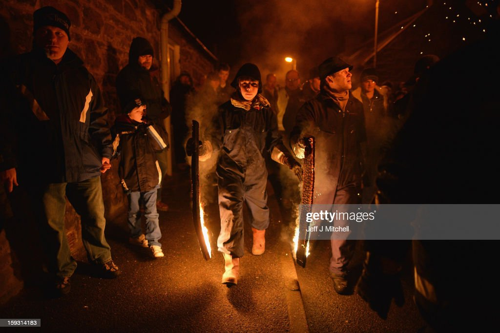 A boy holds burning staves as men from the Clavie Crew take part in The Burning Of The Clavie Festival on January 11, 013 in Burghead, Scotland. The burning of the Clavie takes place on January 11 each year as local people welcome in the New Year with a fire ceremony, which has ancient roots believed to bring good luck for the coming year.