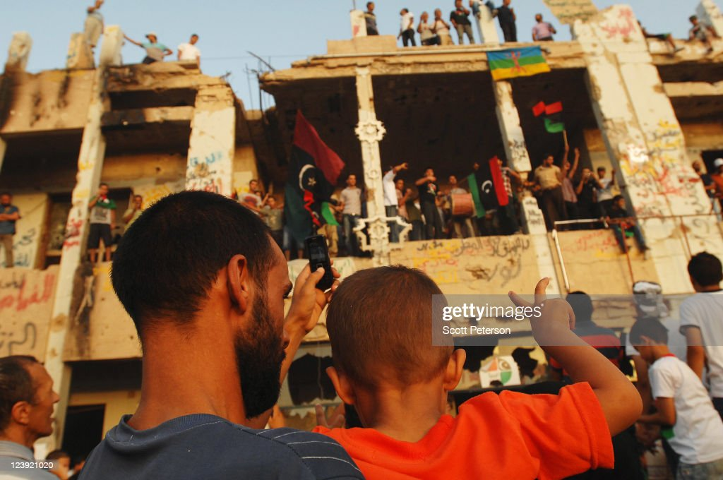 A boy holds his fingers up in a victory sign in front of a Ghaddafi residence as Libyan 'revolution tourists' continue to celebrate the fall of...