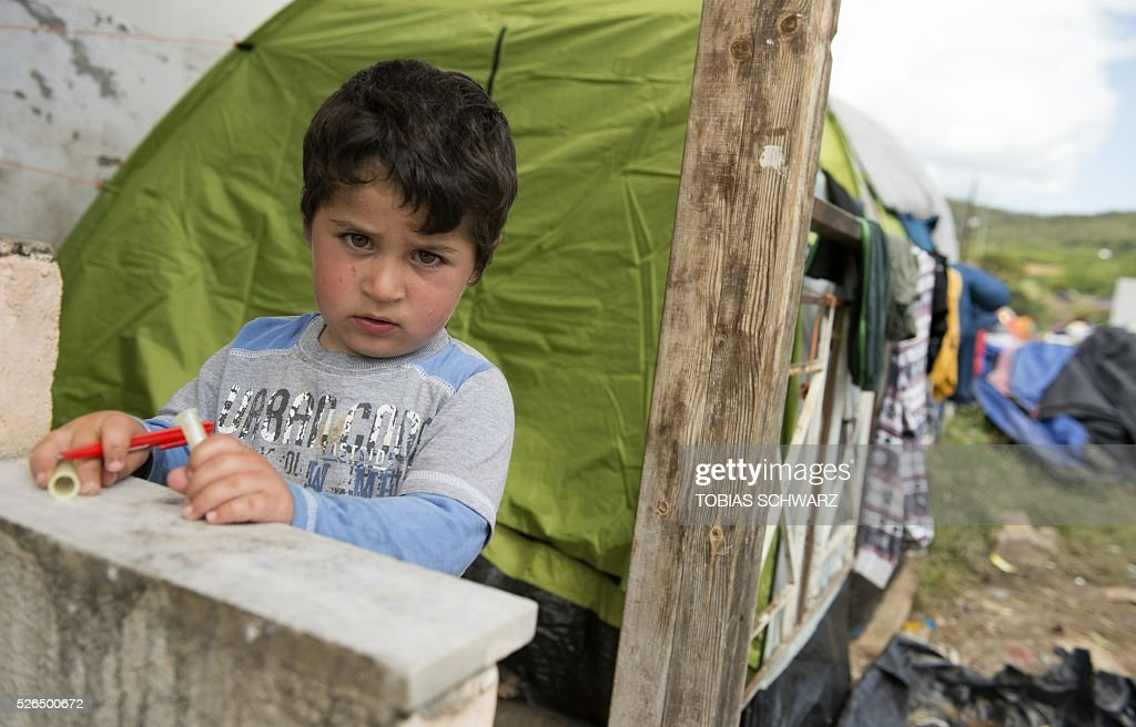 A boy holds pencils as he poses for the photogaphs at a makeshift camp for migrants and refugees near the village of Idomeni not far from the Greek-Macedonian border on April 30, 2016. Some 54,000 people, many of them fleeing the war in Syria, have been stranded on Greek territory since the closure of the migrant route through the Balkans in February. / AFP / TOBIAS