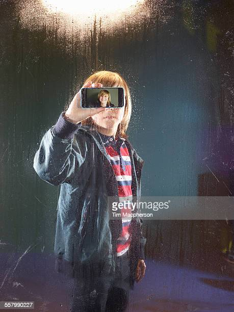 Boy holds phone up to a window