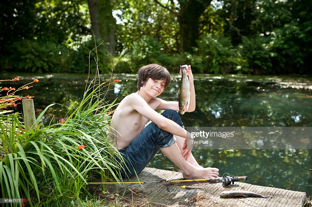Boy holds up a fish he has caught. : Stock Photo