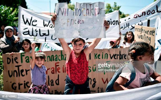 TOPSHOT A boy holds up a placard reading in German 'We only want peace' as refugees mainly coming from Syria protest outside the German embassy in...