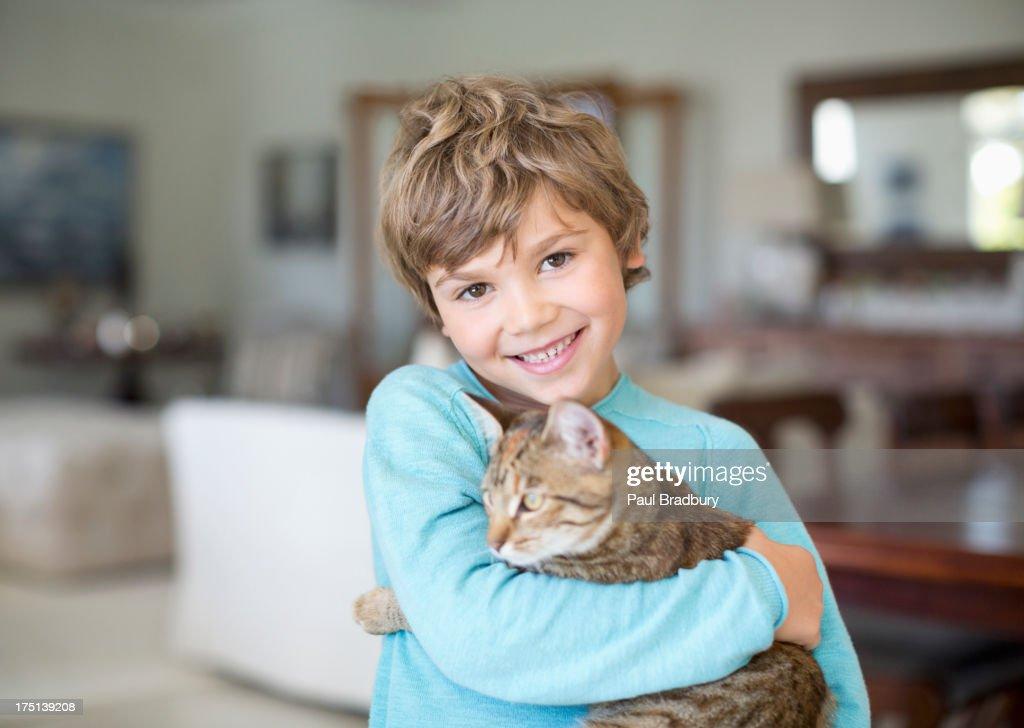 Boy hugging cat in living room : Stock Photo
