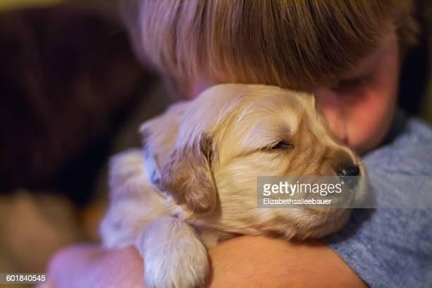 Boy hugging golden retriever puppy dog