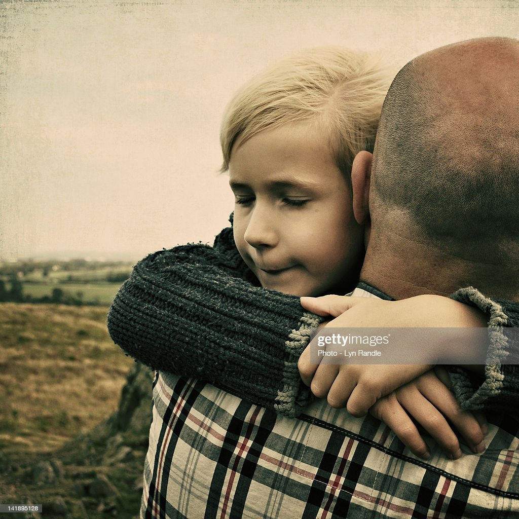 Boy hugging his father : Stock Photo