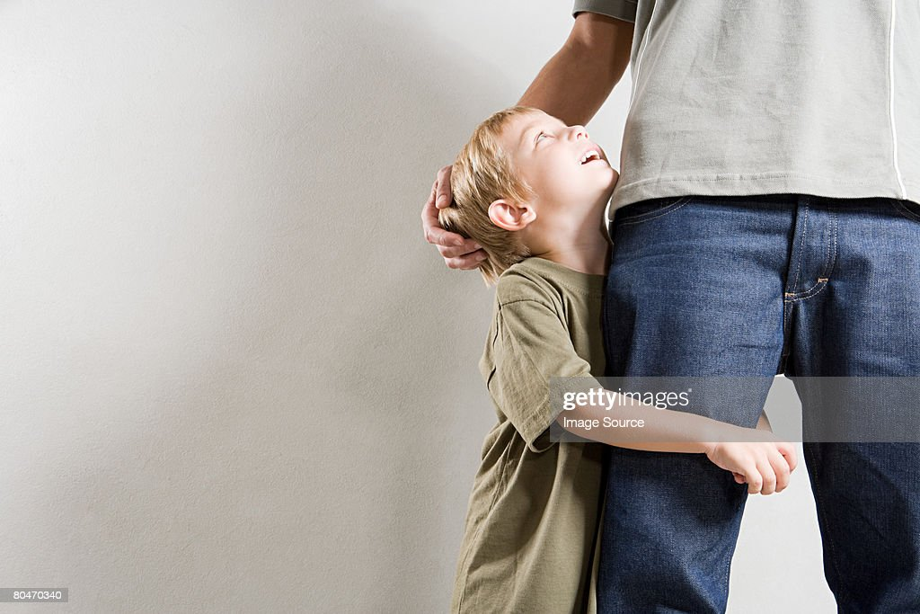 A boy hugging his fathers leg