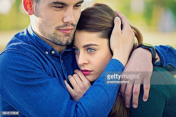 Boy hugging his sad girlfriend in the park
