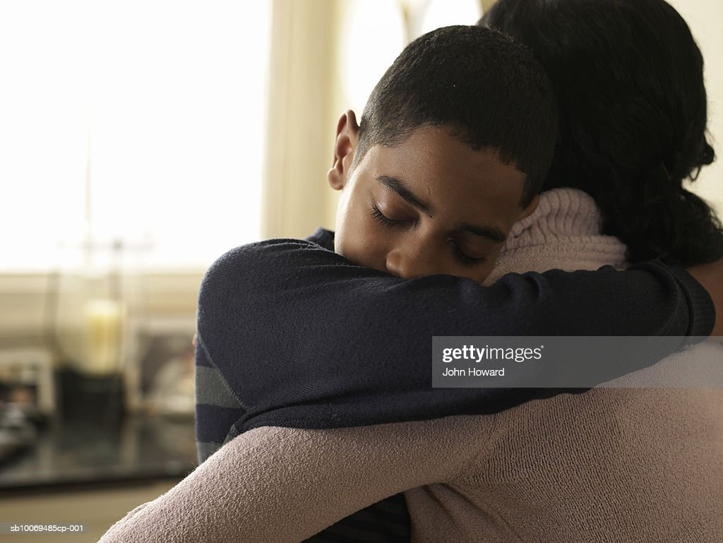 Boy (12-13) hugging mother at home : Stock Photo
