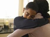 Boy (12-13), que abrazan madre en su hogar
