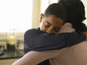 Boy (12-13) hugging mother at home