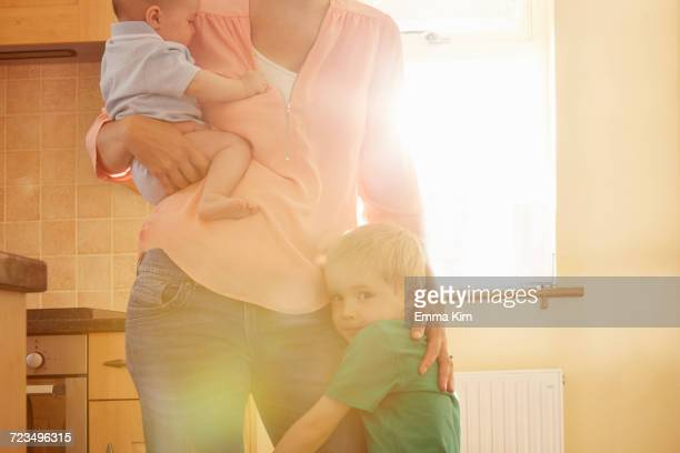 Boy hugging mothers leg while she carries his baby brother in kitchen