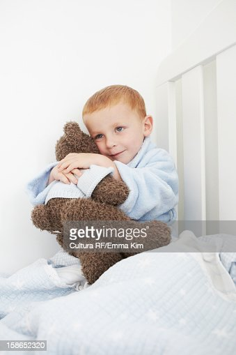 Boy hugging teddy bear in bed : Stock Photo
