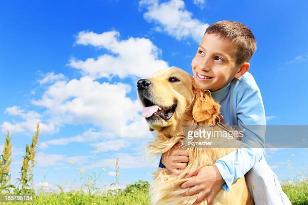 Boy hugs a dog outdoor.