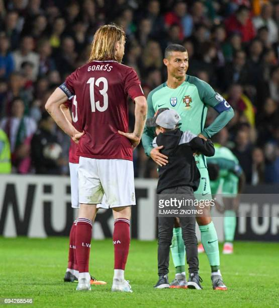 A boy hugs Portugal's Cristiano Ronaldo during the FIFA World Cup 2018 qualification football match between Latvia and Portugal in Riga on June 9...