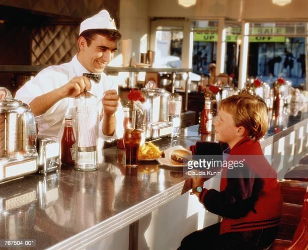 Boy (6-8) in 50's diner, waiter getting straw, USA