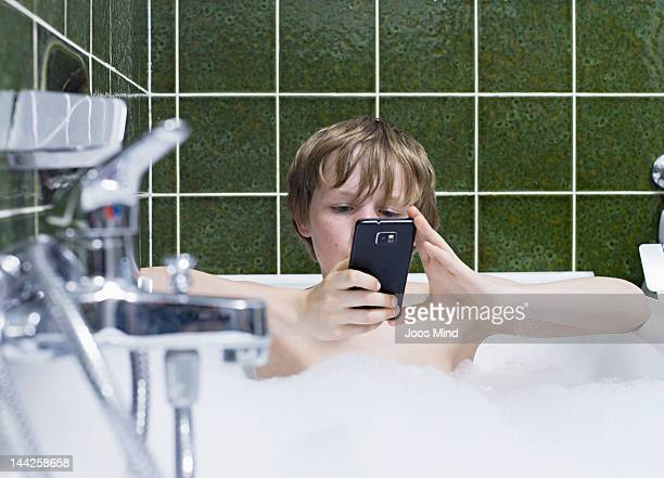 boy in a bubble bath using smart phone