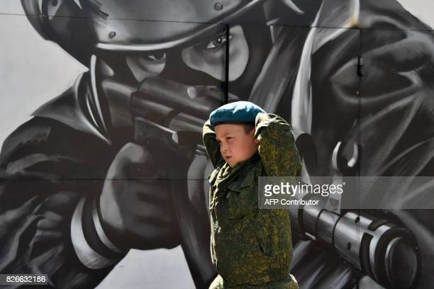 A boy in a camouflage walks past a mural depicting a special forces serviceman during a militarystyle competition organised by the National Guard...