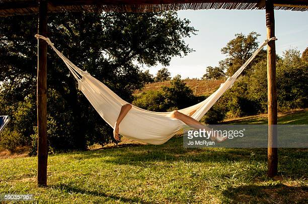 Boy in a hammock, arm and leg sticking out