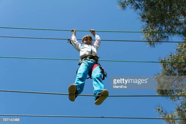 Boy in a harness tightrope walking