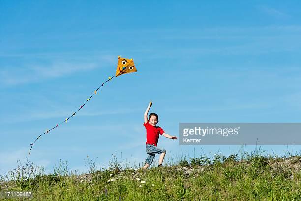 Un garçon dans un T-shirt rouge courir avec un cerf-volant dans la main
