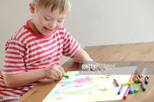 A Boy In Red Stripes Tshirt Coloring With Crayons Stock Photo