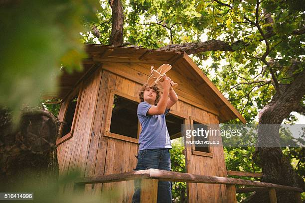 Boy in a treehouse daydreaming with his toy wooden plane