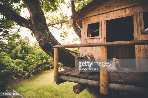 Boy in a treehouse looking in the distance with binoculars