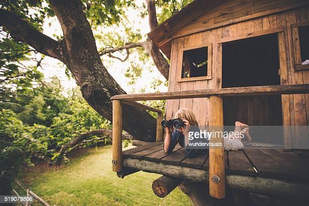 Junge in einem Baumhaus Sie in der Ferne mit Fernglas