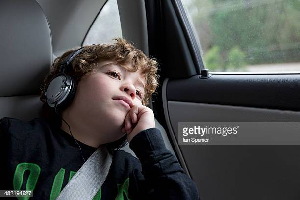 Boy in back seat of car, wearing headphones