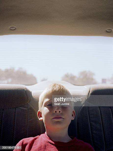 Boy (8-10) in backseat of car, portrait