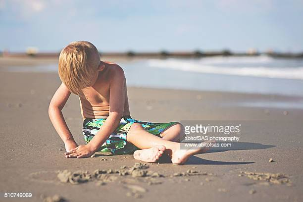 Boy in bathing suit sits on the sand, digging.