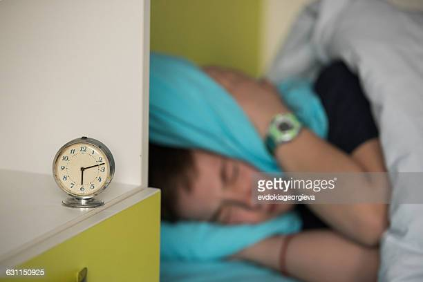 Boy in bed covering his ears while alarm ringing