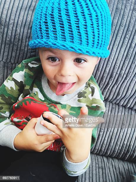 Boy In Blue Knit Hat Sticking Out Tongue On Sofa At Home