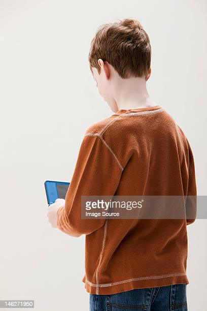 Boy in brown sweater playing hand held video game, studio shot