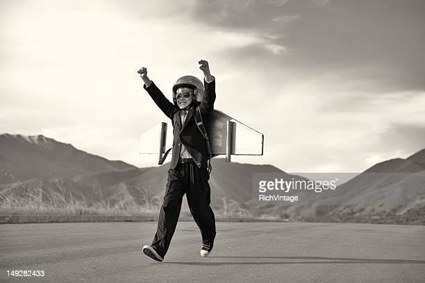 Niño en traje de negocios corriendo con cinturón cohete