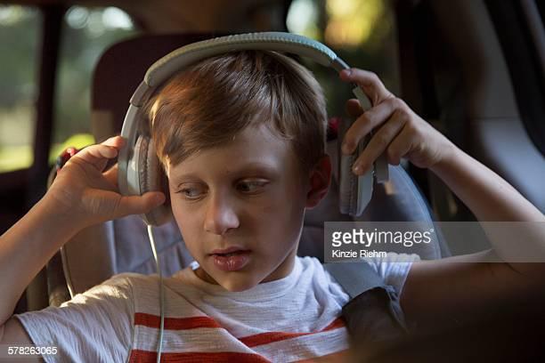 Boy in car back seat removing headphones
